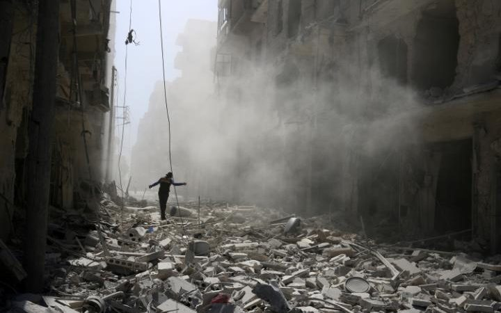 A man walks on the rubble of damaged buildings after an airstrike on the rebel held al-Qaterji neighbourhood of Aleppo, Syria September 25, 2016.  CREDIT:  REUTERS/ABDALRHMAN ISMAIL